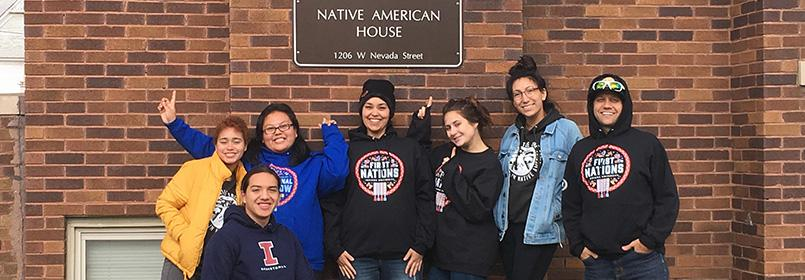 Group of six people smiling for the camera, standing outside the Native American House.