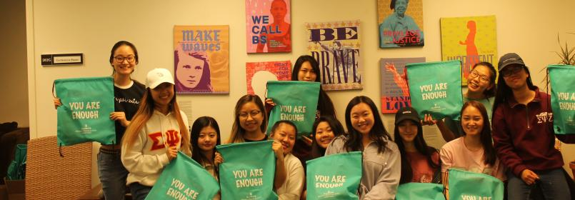 """Picture of several women holding up bags that say """"You are enough"""""""