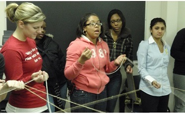 Group of women using yarn for an exercise at a workshop