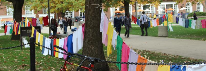 Clothes hanging on a clothesline at the quad with people walking by.