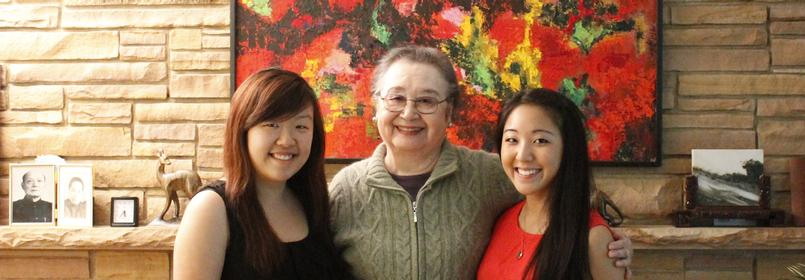 Picture of three people smiling with a colorful piece of art in the background