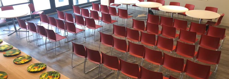 Picture of a room full of red chairs and round tables