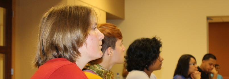 Side view of students listening to a speaker