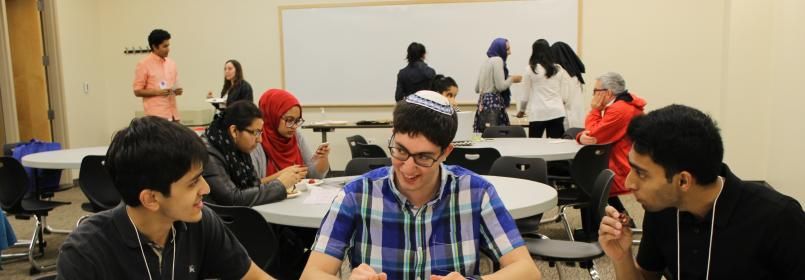 Students conversing at a table, with other students in the background