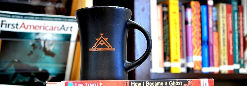 """Picture of a coffee mug that says """"Native American House"""" with a bookshelf full of books in the background."""