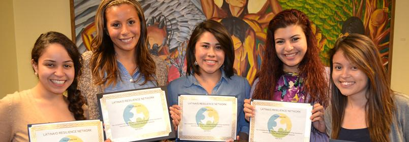 Five women standing side-by-side smiling, posing with certificates