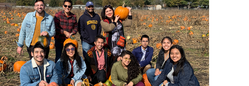 Photograph of a group of happy young people posing in a pumpkin patch. Some are holding pumpkins.