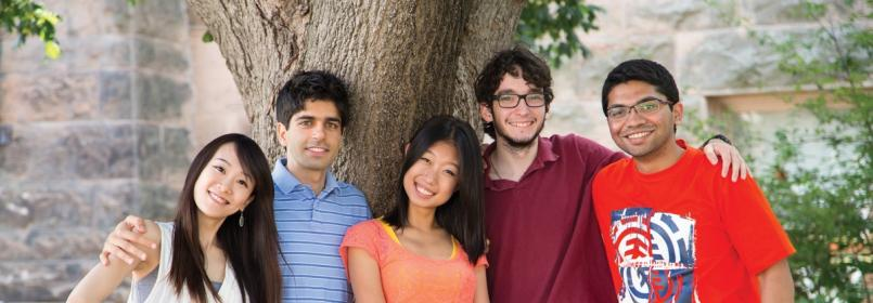 Five smiling students gathered near a tree